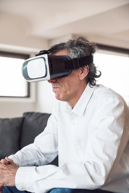 Zijaanzicht van de hogere mens die een virtuele werkelijkheidshoofdtelefoon met behulp van Gratis Foto