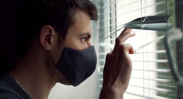 Zijaanzicht van de man in beschermend masker kijkt uit raam door blinds, close-up headshot Premium Foto