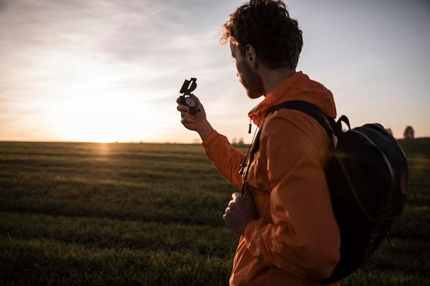 Zijaanzicht van de man op een roadtrip die het uitzicht bewondert terwijl hij een kompas vasthoudt Gratis Foto