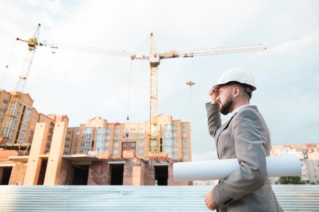 Zijaanzicht van de mannelijke bouwvakker van de ingenieursholding met blauwdruk die zich dichtbij bouwwerf bevinden Gratis Foto