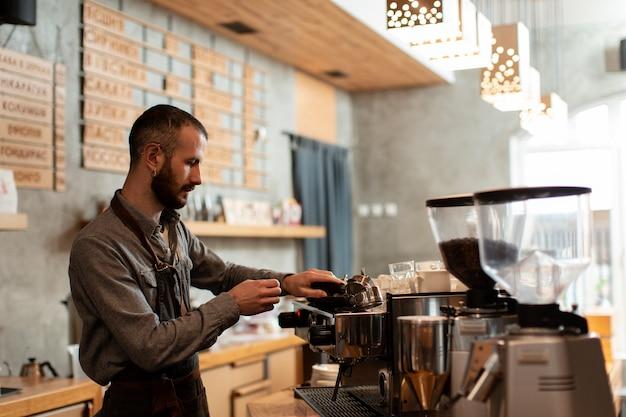 Zijaanzicht van de mens die in koffiewinkel werkt Gratis Foto