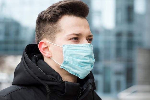 Zijaanzicht van de mens die medisch masker in de stad draagt Gratis Foto