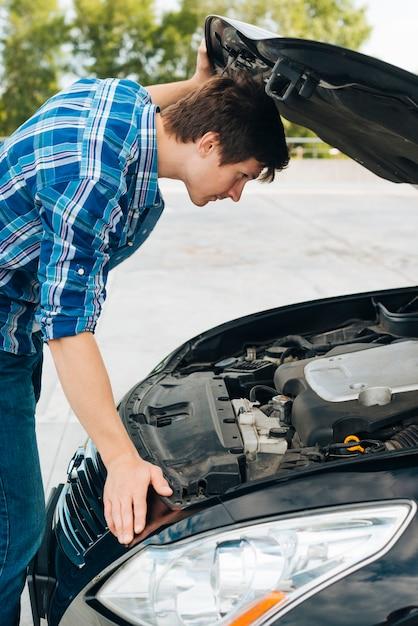 Zijaanzicht van de mens die motor van een auto controleert Gratis Foto