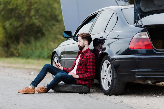 Zijaanzicht van de mens die op auto leunt Gratis Foto