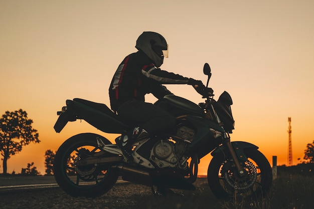 Zijaanzicht van de mens in helm rijden op donkere weg op motor bij zonsondergang op platteland Premium Foto