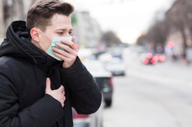 Zijaanzicht van de mens in stad hoesten terwijl het dragen van een medisch masker Gratis Foto