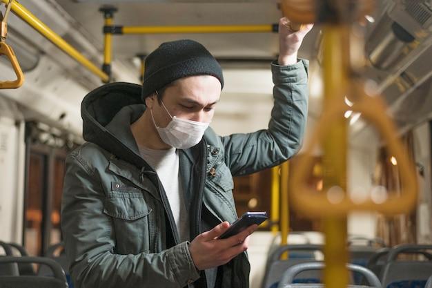 Zijaanzicht van de mens met medisch masker dat zijn telefoon op de bus bekijkt Gratis Foto