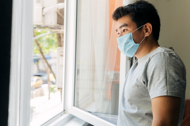 Zijaanzicht van de mens met medisch masker thuis tijdens de pandemie die door het venster kijkt Gratis Foto