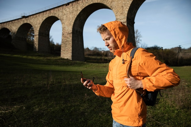 Zijaanzicht van de mens op een roadtrip poseren voor aquaduct terwijl hij kompas vasthoudt Premium Foto