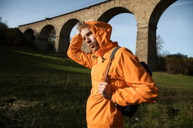 Zijaanzicht van de mens op een roadtrip poseren voor aquaduct Premium Foto