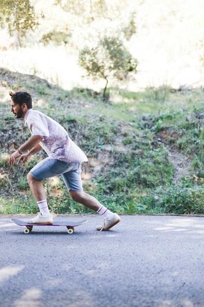 Zijaanzicht van de mens op skateboard Gratis Foto