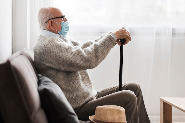Zijaanzicht van de oude man met medisch masker in een verpleeghuis Gratis Foto