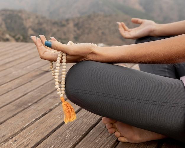 Zijaanzicht van de vrouw die buiten yoga doet en rozenkrans houdt Gratis Foto