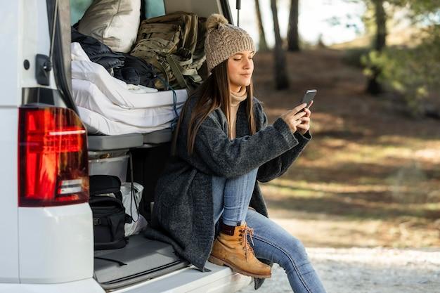 Zijaanzicht van de vrouw die in de kofferbak van de auto zit tijdens een roadtrip en smartphone gebruikt Gratis Foto