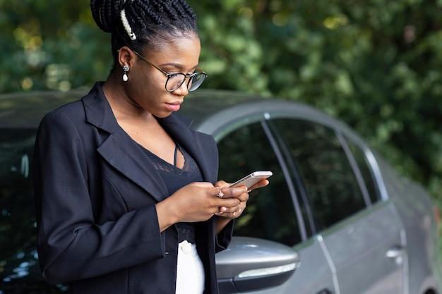 Zijaanzicht van de vrouw die op haar auto rust tijdens het kijken naar smartphone Gratis Foto