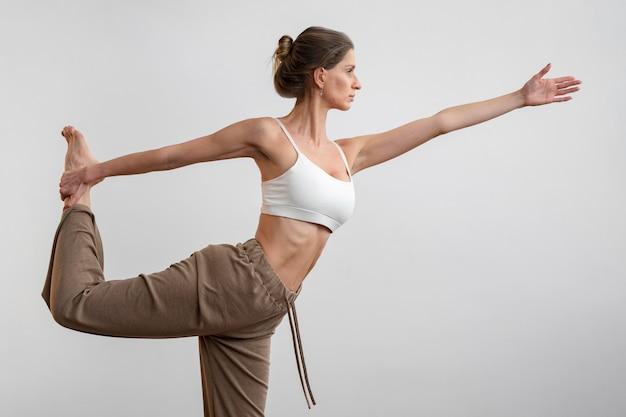 Zijaanzicht van de vrouw die thuis yoga beoefent Gratis Foto