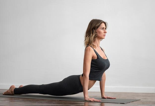 Zijaanzicht van de vrouw die thuis yoga doet Gratis Foto