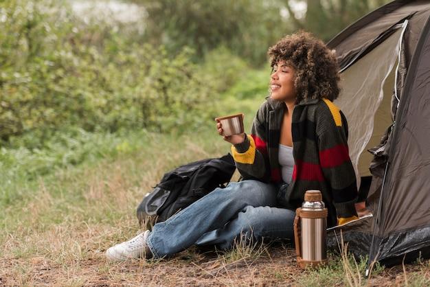 Zijaanzicht van de vrouw die van het uitzicht geniet tijdens het kamperen buiten Gratis Foto