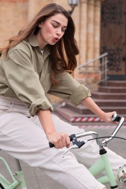 Zijaanzicht van de vrouw haar fiets in de stad buiten rijden Gratis Foto