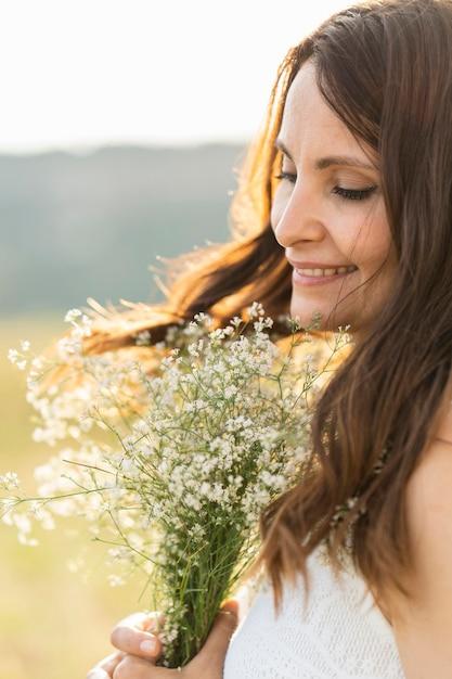 Zijaanzicht van de vrouw in de natuur met boeket bloemen Gratis Foto