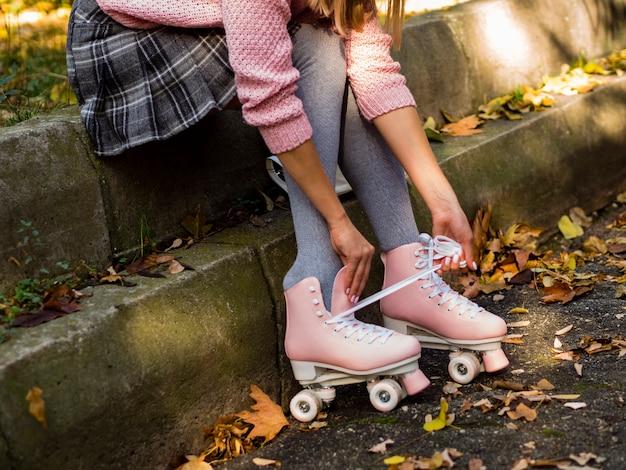 Zijaanzicht van de vrouw in rolschaatsen en bladeren Gratis Foto
