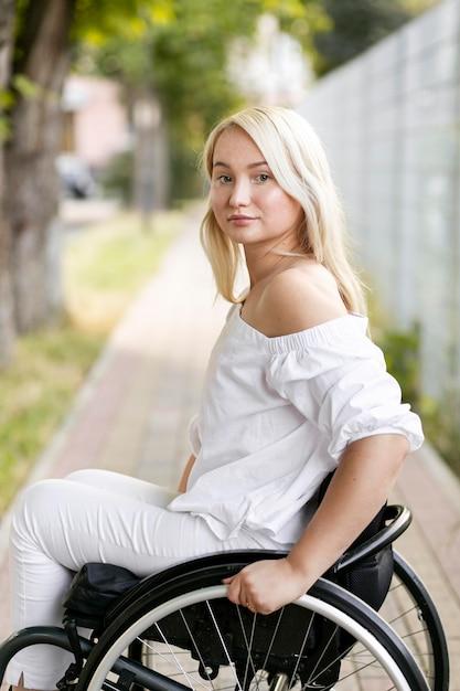 Zijaanzicht van de vrouw in rolstoel buitenshuis Gratis Foto