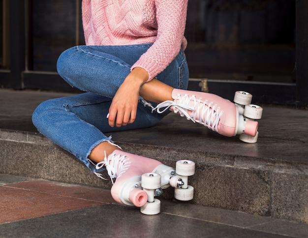 Zijaanzicht van de vrouw in spijkerbroek op trappen met rolschaatsen Gratis Foto