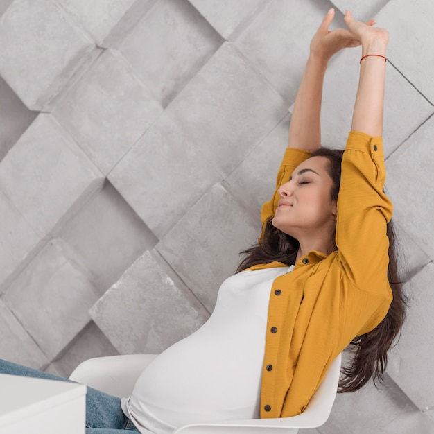 Zijaanzicht van de zwangere vrouw die zich uitstrekt terwijl op stoel thuis Gratis Foto