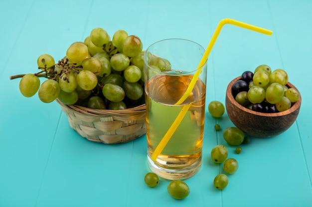 Zijaanzicht van druivensap met drinkbuis in glas en mand van druivenmost met druivenbessen in kom op blauwe achtergrond Gratis Foto