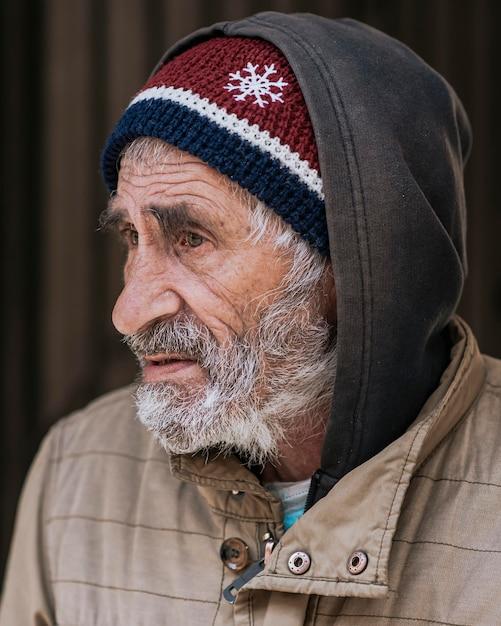 Zijaanzicht van een bebaarde dakloze man Gratis Foto