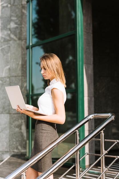 Zijaanzicht van een blonde jonge onderneemster die zich voor bureau bevindt dat laptop bekijkt Gratis Foto