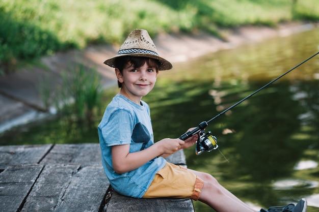 Zijaanzicht van een gelukkige jongen die hoed draagt die op meer vissen Gratis Foto