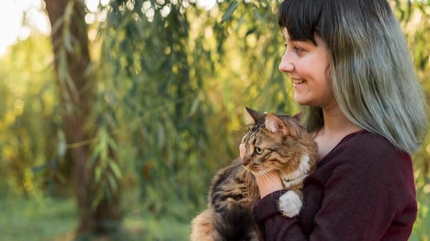 Zijaanzicht van een geverfde haarvrouw die haar gestreepte katkat in bos omhelzen Gratis Foto
