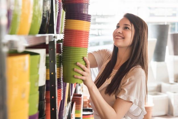 Zijaanzicht van een glimlachende jonge vrouw die bloeiende installaties in plank schikken Gratis Foto