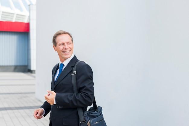 Zijaanzicht van een glimlachende volwassen zakenman in openlucht Gratis Foto