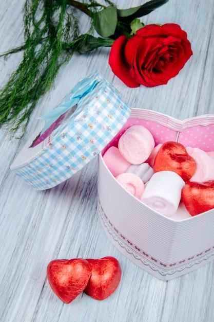 Zijaanzicht van een hartvormige geschenkdoos gevuld met roze marshmallow en chocolade snoepjes verpakt in rode folie en rood roze bloem op grijze houten tafel Gratis Foto
