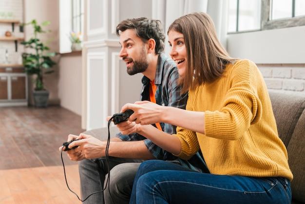 Zijaanzicht van een jong paar die het videospelletje thuis spelen Gratis Foto