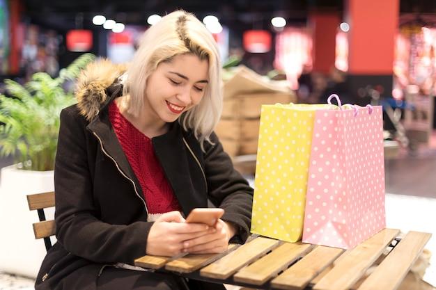 Zijaanzicht van een jonge glimlachende vrouwenzitting op koffiebar Premium Foto