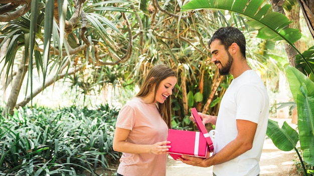 Zijaanzicht van een jonge man die geschenk aan zijn vriendin Gratis Foto
