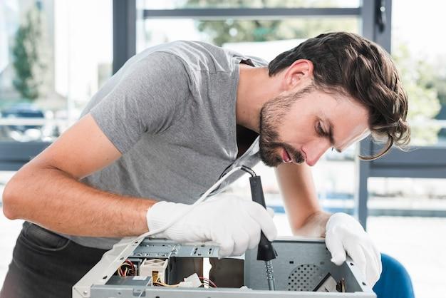 Zijaanzicht van een jonge mannelijke technicus die aan gebroken computer werkt Gratis Foto