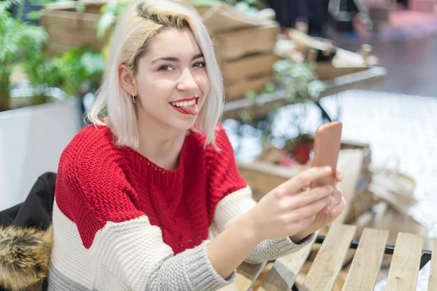 Zijaanzicht van een jonge mooie vrouw die een selfie in een bar neemt. Premium Foto