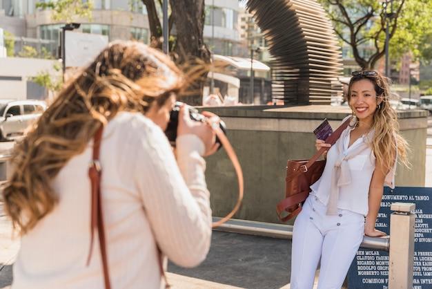 Zijaanzicht van een jonge vrouw die foto van haar vriend neemt die op traliewerk leunt Gratis Foto