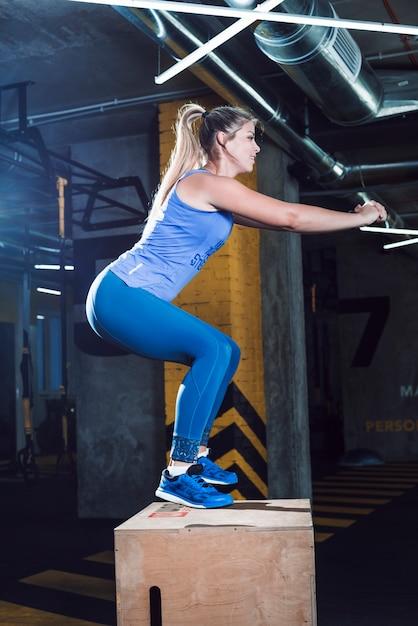 Zijaanzicht van een jonge vrouw die hurkende oefening op houten doos in gymnastiek doet Gratis Foto