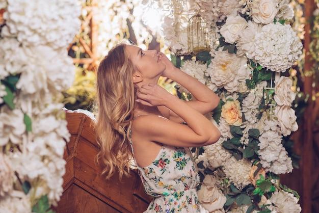 Zijaanzicht van een jonge vrouw die omhoog witte bloemendecoratie bekijken in de tuin Gratis Foto