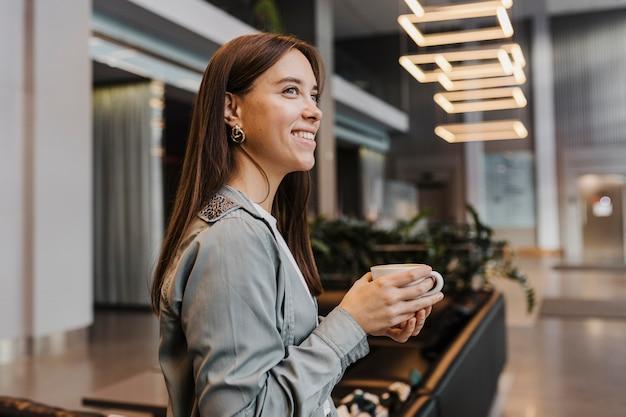 Zijaanzicht van een jonge vrouw die van koffie geniet Premium Foto
