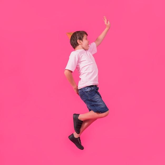 Zijaanzicht van een jongen in feesthoed die tegen roze achtergrond springt Gratis Foto