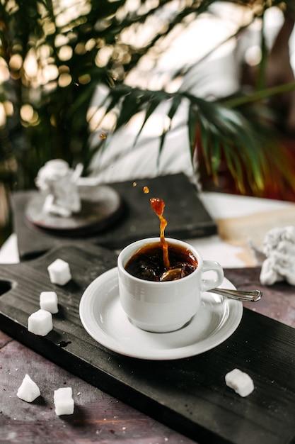 Zijaanzicht van een kopje koffie op een houten snijplank Gratis Foto