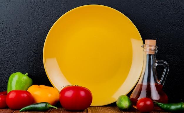 Zijaanzicht van een lege gele plaat en tomaten van verse groenten de kleurrijke groene paprika's en een fles olijfolie bij dark Gratis Foto