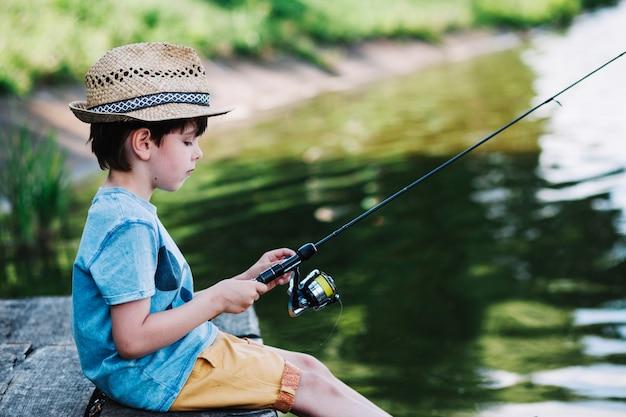 Zijaanzicht van een leuke jongen die op meer vissen Gratis Foto