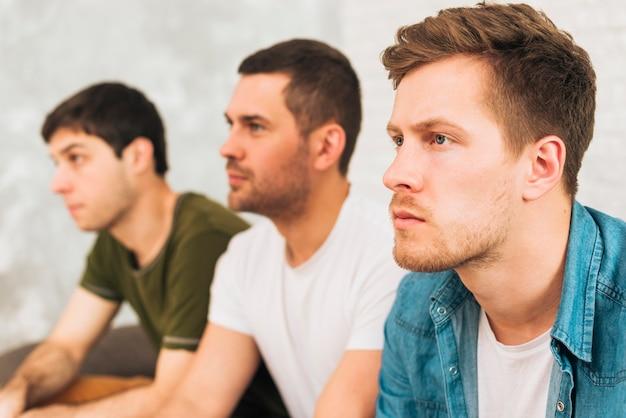 Zijaanzicht van een man televisie kijken met hun vrienden Gratis Foto